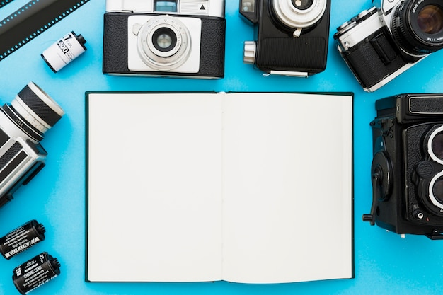 Cameras and film near blank notebook