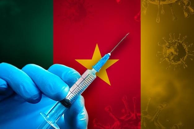 카메룬 코비드19 예방 접종 캠페인 파란색 고무 장갑을 끼고 깃발 앞에 주사기를 들고 있습니다