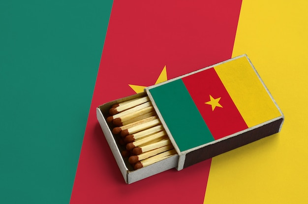 Cameroon flag  is shown in an open matchbox, which is filled with matches and lies on a large flag