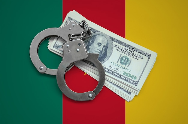 Cameroon flag  with handcuffs and a bundle of dollars. currency corruption in the country. financial crimes