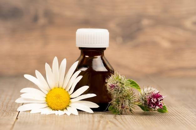 Цветы ромашки и лопуха с эфирным маслом в коричневых стеклянных бутылках на деревянном деревенском столе