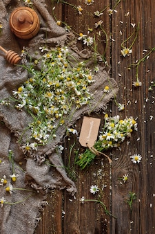 Camomile on canvas. top view on vintage wood background