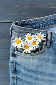 Цветы ромашки в кармане джинсов.