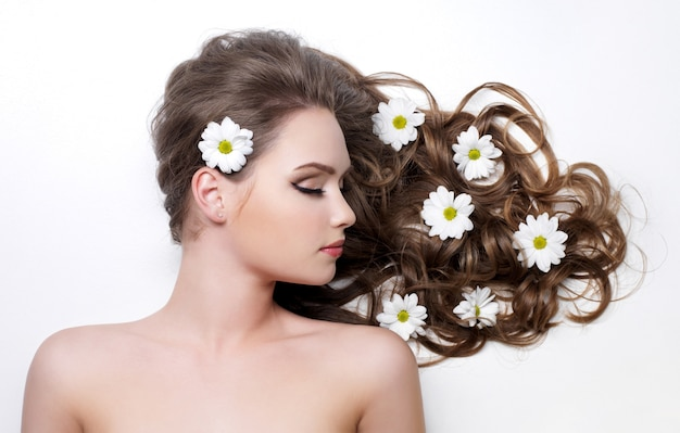 Ромашки в красивых великолепных длинных вьющихся волосах молодой женщины - белое пространство