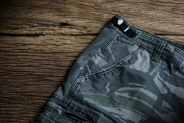 Camouflage pattern pants on wooden background