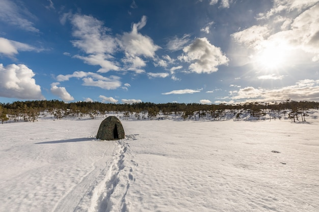 Camouflage tent on a snow covered bog with cloudy sky