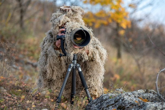 Camouflage wildlife photographer in the ghillie suit working in the wild