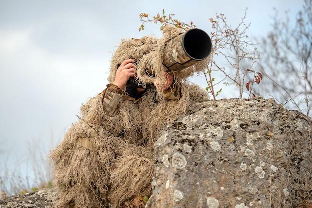 野生で働くギリースーツのカモフラージュ野生生物写真家