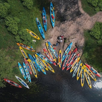 Camp and pier of tourist kayaks top view shot over the river bank, camp during kayaking on the river