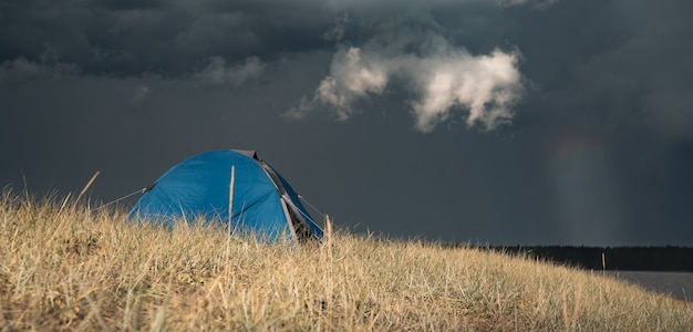 丘の上のキャンプテント。雷雲