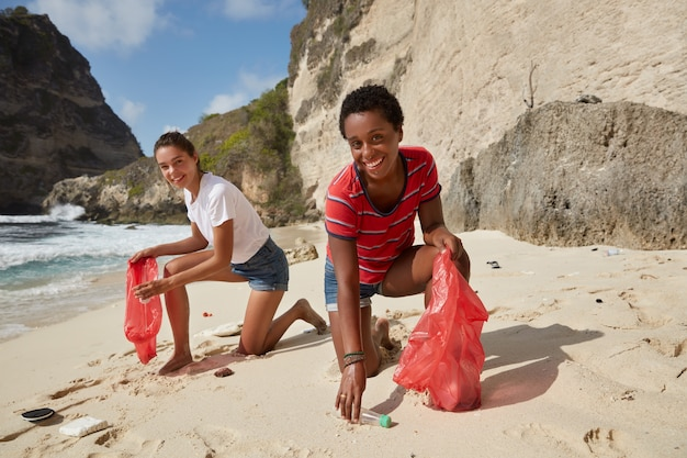 私たちの環境をきれいにするためのキャンペーン。幸せな多様な女性がペットボトルを拾う
