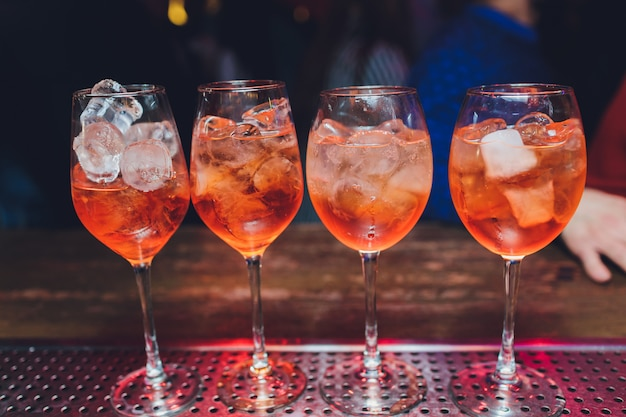 캄 파리 토닉 알코올 칵테일, 레드 비터, 토닉, 라임, 아이스. 오래 된 나무 테이블 배경, 바 도구, 선택적 초점. 모든 이름은 상표가 아닌 칵테일을 나타냅니다.