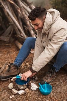 Concetto di vita del campeggiatore con l'uomo che cucina in natura