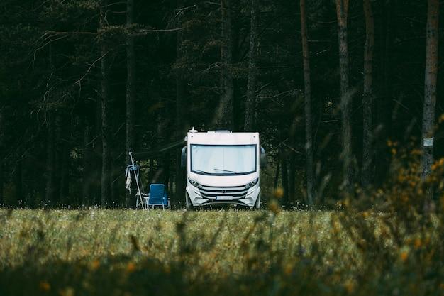 森の森を背景に自然の中に駐車したキャンピングカー-フリーライフスタイルの屋外休暇の人々と家族の概念-旅行の概念を楽しんでいます