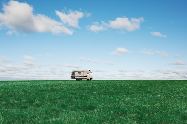 雲と青空の背景に緑の野原でキャンピングカー。自然にキャンピングカー。旅行