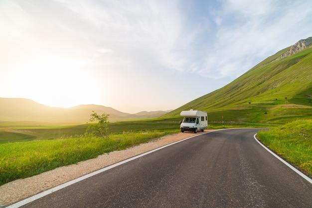 아름 다운 풍경에 길가에 캠퍼 밴. 일몰의 극적인 하늘, 이탈리아의 독특한 고원과 언덕 위의 아름다운 구름, 대안적인 반라이프 휴가 개념.