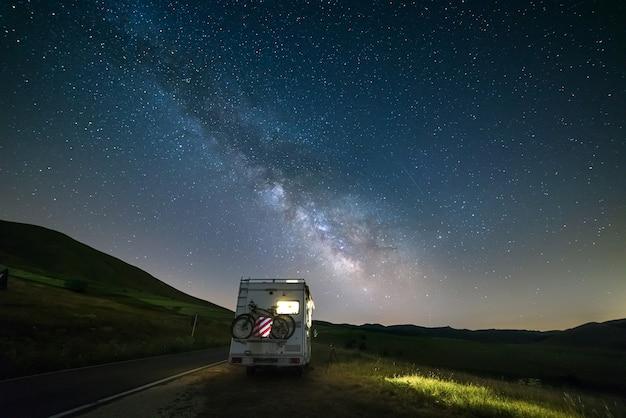 별 아래 아름다운 밤 풍경에 길가에 캠퍼 밴. 조명이 켜진 캠핑카 위로 은하수 호와 별이 보입니다. 이탈리아 apennines에서 캠핑의 자유.
