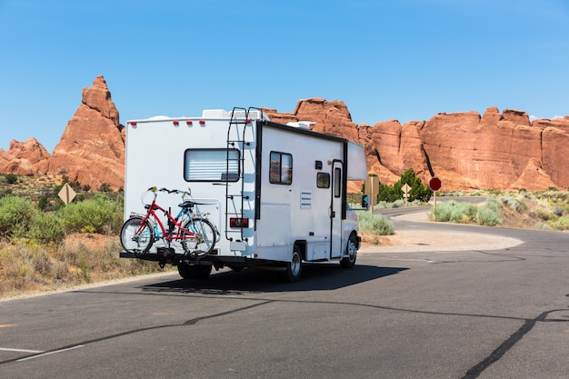 Camper with bikes on asphalt road. rocky mountains on the background.