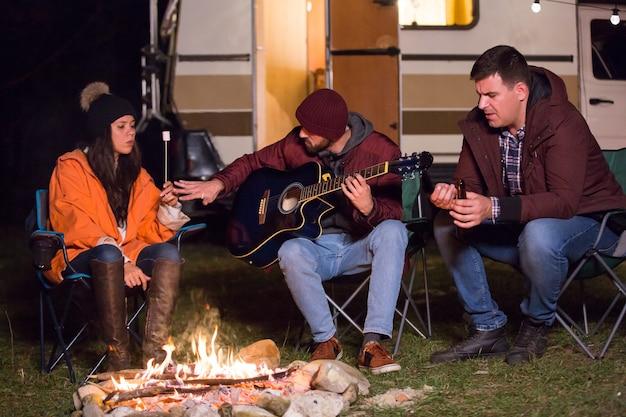 Отдыхающие играют на гитаре и жарят зефир в кемпинге в горах. ретро автофургон.