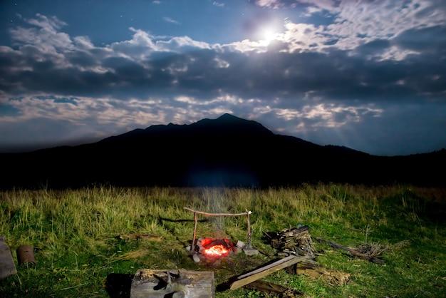 暗い空と月の光で夜の山の近くの緑の芝生のキャンプファイヤー