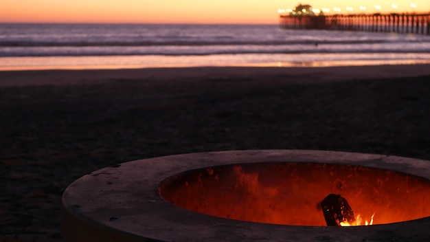 Campfire pit by oceanside pier, california usa. camp fire burning on ocean beach, bonfire flame in cement ring place for bbq, sea water waves. romantic evening twilight sky, dusk after summer sunset.