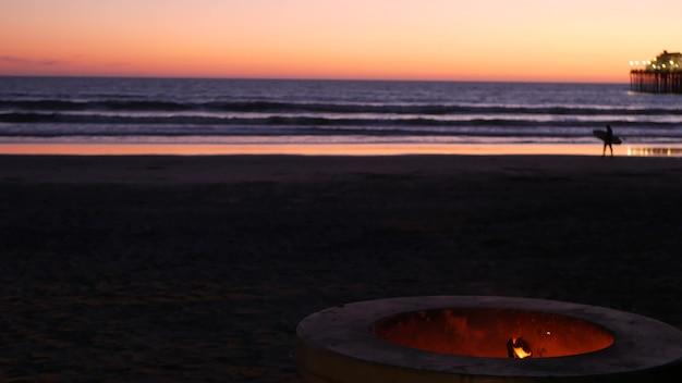 米国カリフォルニア州オーシャンサイド埠頭のキャンプファイヤーピット。オーシャンビーチで燃えるキャンプファイヤー、バーベキュー用のセメントリングの場所での焚き火の炎、海水の波。ロマンチックな夕方の夕暮れの夕暮れの空。サーフボード付きサーファー