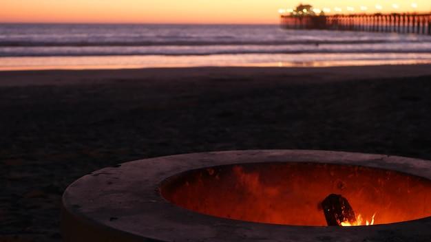 米国カリフォルニア州オーシャンサイド埠頭のキャンプファイヤーピット。オーシャンビーチで燃えるキャンプファイヤー、バーベキュー用のセメントリングの場所での焚き火の炎、海水の波。ロマンチックな夕方の夕暮れの空、夏の日没後の夕暮れ。