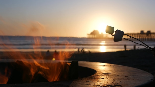 Campfire pit by oceanside pier, california usa. camp fire on ocean beach, bonfire flame in cement ring place for bbq, sea water waves. heating, roast or toast marshmallow on stick. romantic sunset sky
