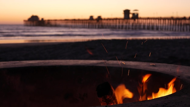 Campfire pit in california usa. camp fire on twilight ocean beach, bonfire flame by sea water waves.