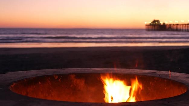 미국 캘리포니아의 캠프파이어 구덩이. 황혼의 바다 해변에서 캠프 파이어, 바닷물 파도에 의한 모닥불 불꽃.