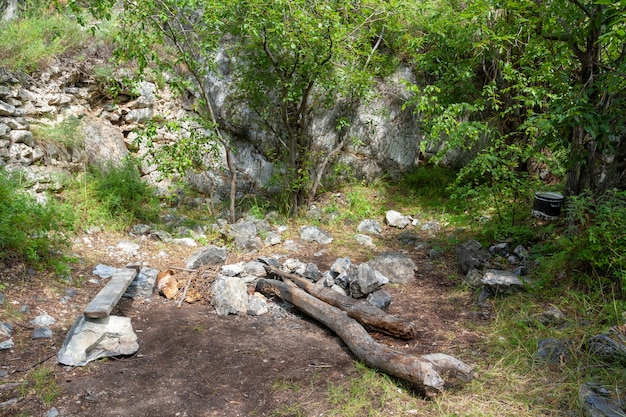 Campfire place under rock with bench and tree trunks. bowler hat hangs on branch of tree. large stones and green vegetation around.