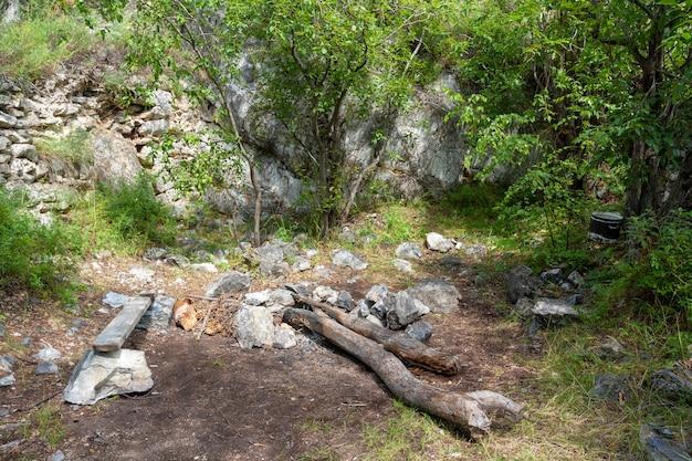 Место для костра под скалой со скамейкой и стволами деревьев. котелок висит на ветке дерева. вокруг большие камни и зеленая растительность.