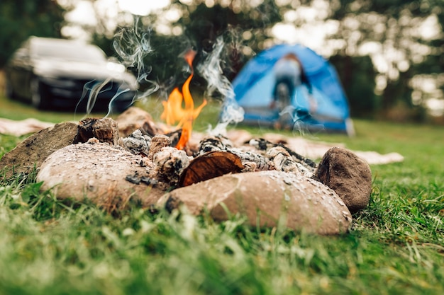 Campfire and tent on background