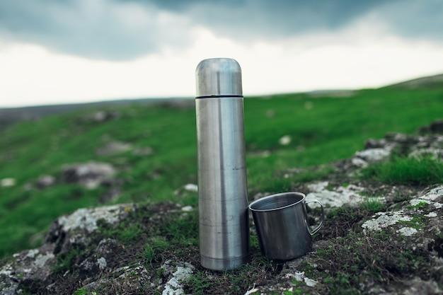 캠핑 및 여행 개념. 강철 보온병과 산의 녹색 필드에 돌에 스테인리스 컵의 근접.