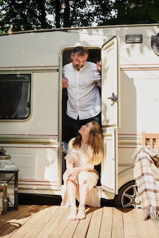 キャンプや旅行。幸せなカップルの屋外旅行でトレーラー男と女の近くに屋外でリラックス