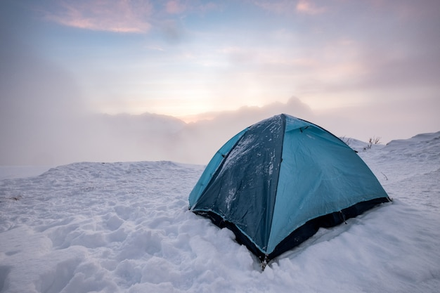 Camping blue tent at snowy hill in foggy