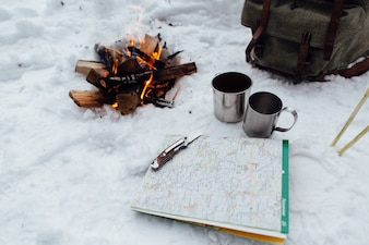 Camping. Bonfire with two mugs, map and knife on snow