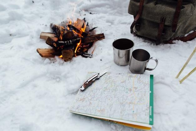 Campeggio. falò con due tazze, mappa e coltello sulla neve