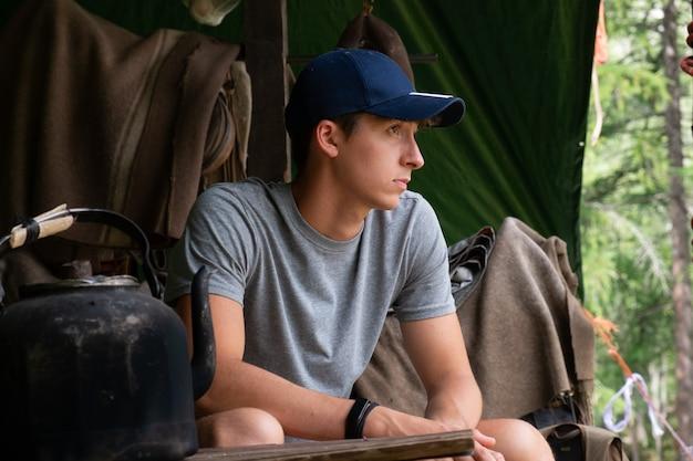 荒野で野外生活帽子をかぶったキャンプ少年自然の中で瞑想する若い男
