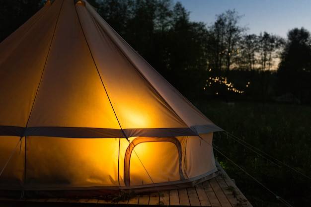 Camping canvas bell tent glows at night