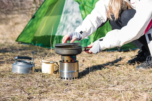 Camping and cooking. woman hiker cooking lunch in front of her tent in nature