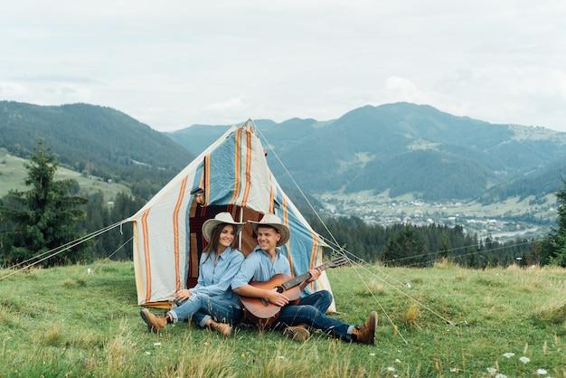 Кемпинг пара в палатке сидит, глядя на вид в горах
