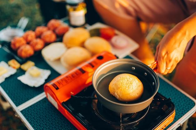 Приготовление еды в кемпинге. гамбургеры на сковороде на туристической пожарной плите. лагерь готовки на берегу озера.