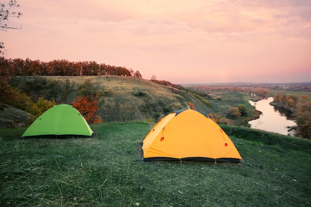 Camping from orange and green tents on banks of river
