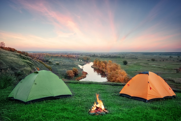 Camping from orange and green tents with fire on banks of river