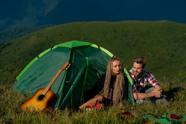 Camping happy man and woman smiling and playing songs at the guitar while camping in mountains