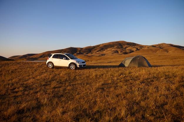 야생의 자연 속에서 캠핑. 텐트 옆 계곡 중간에 주차 된 흰색 현대 자동차. 관광객은 야외에서 휴식을 취하고 여행 중 휴식을 취합니다. 푸른 하늘과 갈색 산의 아름다운 풍경