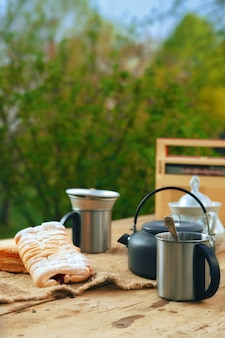 Camping kettle with a mug and biscuit on the table