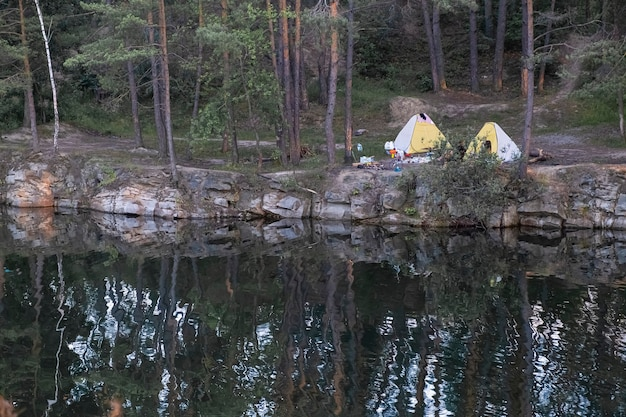 Camping on the lake. view of tourist tents located on the edge of a flooded granite quarry among pine trees