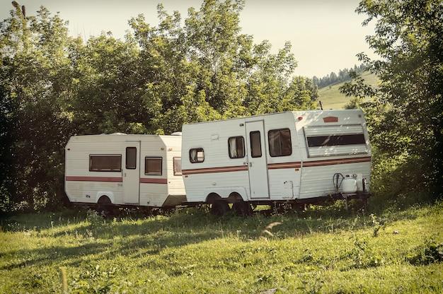 Кемпинг с караванами в природном парке. кемпинг трейлеры на траве на фоне гор